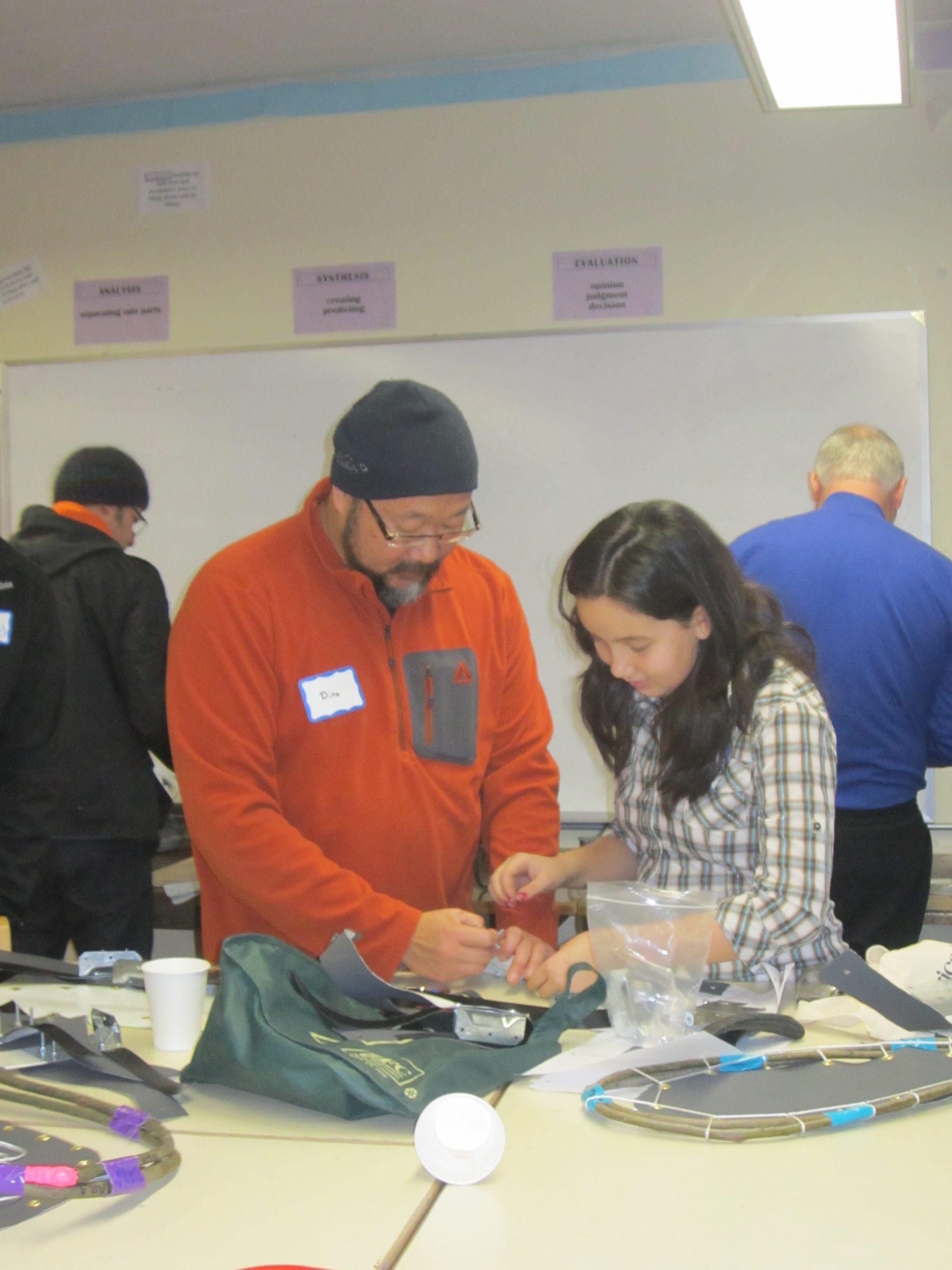 Parents volunteer to help build snow shoes.