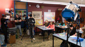 Director in action in classroom scene.