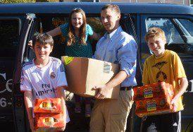 Math and Advisory Teacher, Jon Howland, loading the White Center Food Bank van with his Advisory students.